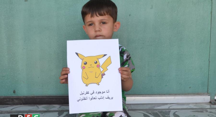 Den syriske gruppe RFS, der kæmper for at få syriske børns vilkår på dagsordenen, har offentliggjort en række billeder af syriske børn med tegninger af Pokémoner. På tegningerne står der på arabisk præcis, hvor i landet de befinder sig, sammen med teksten: »Jeg er her, kom og red mig«. Foto: RFS på Twitter.