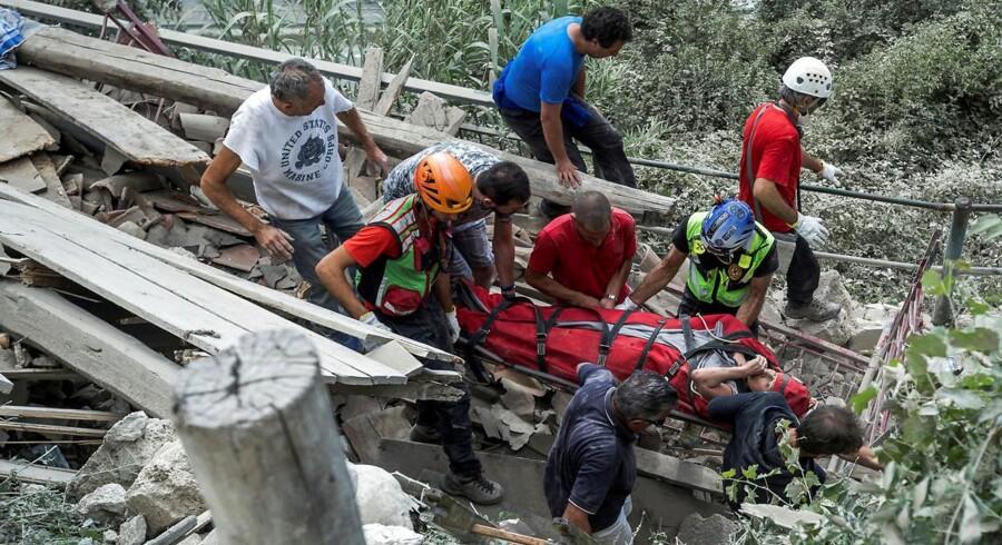 Redningsmandskab hjælper en såret person i Pescara del Tronto.
