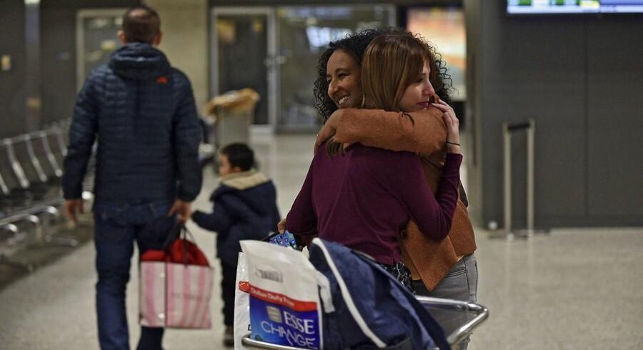 Irakeren Roslyn Sinha, 30, giver sin advokat et kram efter domskendelse har ophævet Trumps indrejseforbud til USA. Hun er boet med sin mand i Texas de seneste seks måneder og er i en prices med at søge greencard ti USA. Den dag hvor Trump udstedet sit indrejseforbud fløj huun til Dubai for at besøge sin syge mor - men kunne derefter ikke flyve tibage til USA. Men det kan hun nu.