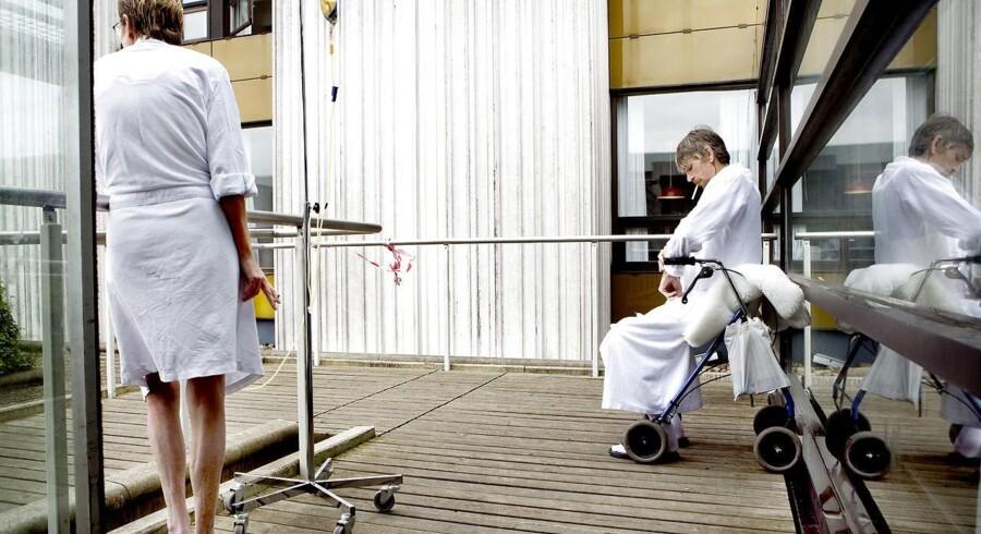 Patienter i hvide badekåber ryger udenfor Hvidovre Hospital.
