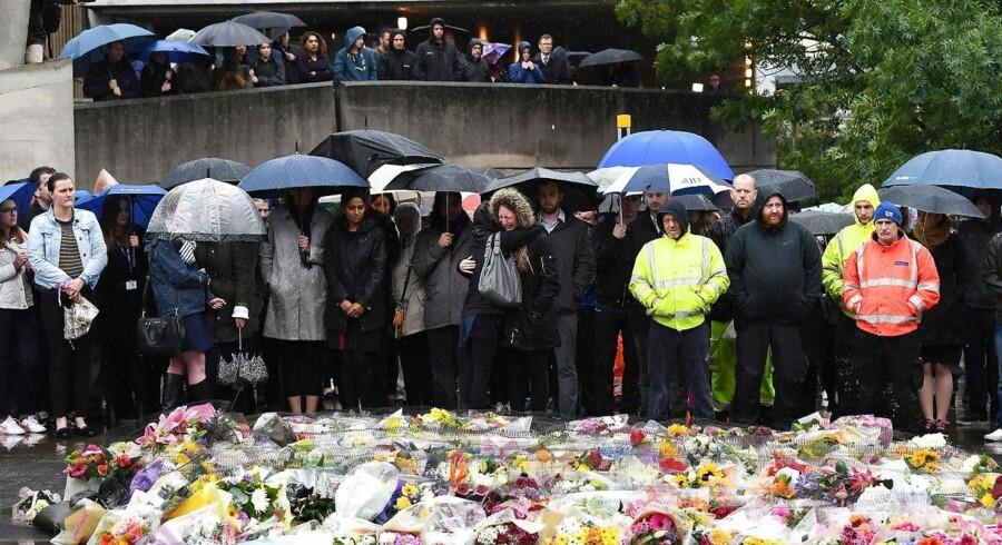 Folk holder et minuts stilhed ved London Bridge, hvor der er lagt blomster efter terrorangrebet lørdag aften, hvor syv personer blev dræbt og 48 såret. / AFP PHOTO / Justin TALLIS