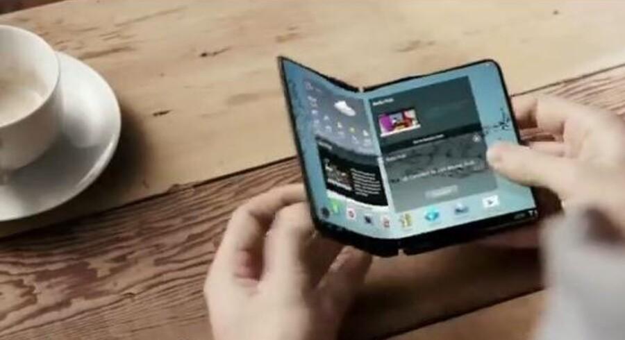 Mobiltelefonens skærm skal kunne foldes sammen, når man ikke bruger den, f.eks. når man taler. Eller den skal kunne foldes ud og blive endnu større. Begge dele rumler verdens største mobilproducent med at gøre klar, måske allerede til februar. Allerede i 2013 blev visionen præsenteret på verdens største forbrugerelektronikmesse af Samsung. Foto fra Samsung-video