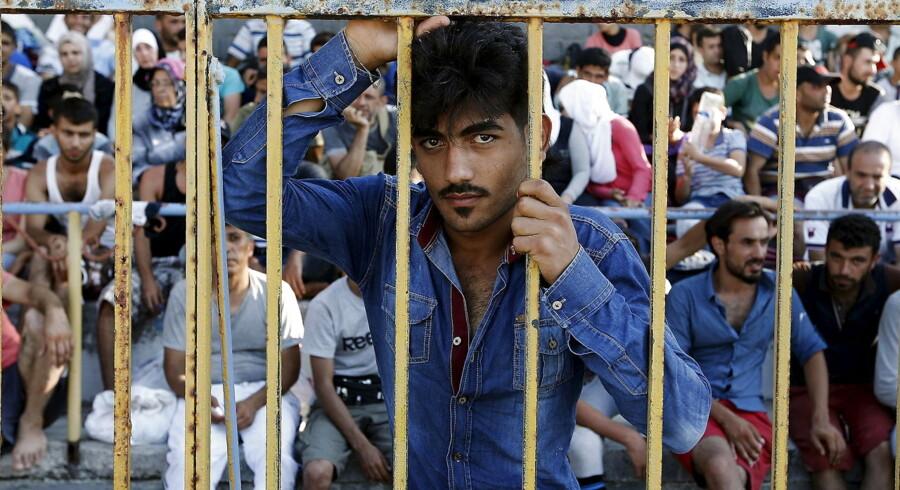 Afghanske og syriske flygtninge er lukket inde på et stadion på Kos, mens politiet registrerer dem.