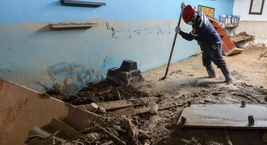 En brandmand leder efter flere ofre i et de huse, hvor mudderet er skyllet ind. Scanpix/Luis Robayo