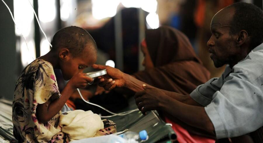 Arkivfoto fra 2011. Mogadishu: En far hjælper sin 5-årige datter Maryam med at drikke sin medicin mod kolera.