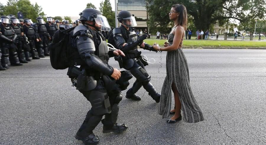 En ukendt kvindelig demonstrant blev fanget i dette billede, han hun på stilfærdig vis protesterede foran to amerikanske politibejtente under »Black Lives Matters«-demonstrationen i Baton Rouge, Louisiana, 9. juli.