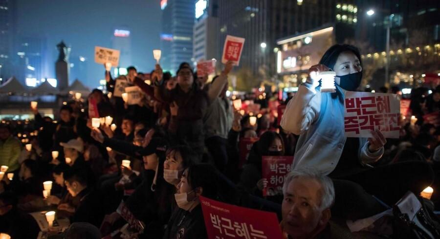 I flere uger har der været store demonstrationer i Sydkoreas hovedstad, Seoul, for at få præsidenten til at gå af oven på en skandale, som bliver ved med at udvikle sig. Arkivfoto: Ed Jones, AFP/Scanpix