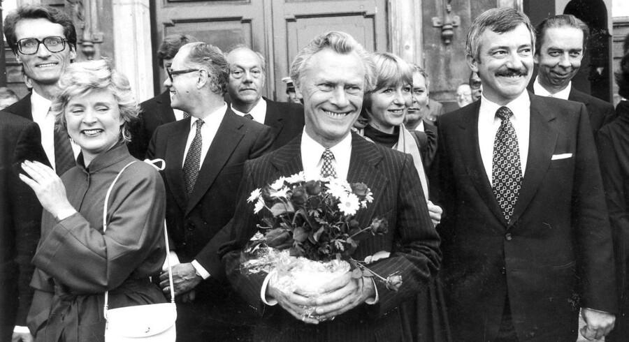 Poul Schlüter efter audiens hos dronningen med sin fireparti-regering i september 1982. Bag Schlüter til højre ses den nye kulturminister, Mimi Jakobsen (CD), der sad i Kulturministeriet til marts 1986. Kort inden folketingsvalget i 1987 blev hun udnævnt til minister for Grønland - en post hun grundet valget kun nåede at besidde i ni dage. Dermed er Mimi Jakobsen den minister, der har siddet kortest tid på en ministerpost.På billedet ses fra venstre: Bertel Haarder, Grethe Fenger Moeller, H.P. Clausen, Christian Christensen, Poul Schluter (med blomsterbuket), Mimi Jakobsen, Uffe Ellemann-Jensen og Niels Anker Kofoed.