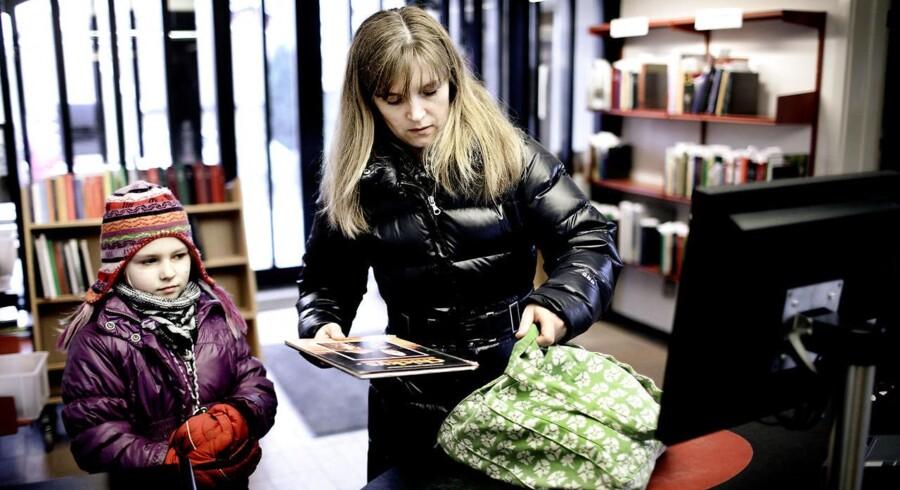 Mor og datter låner bøger på biblioteket.