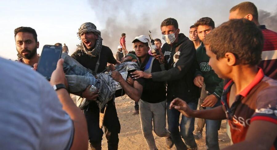 Palæstinensere bærer en såret væk under demonstrationer i Gaza-striben i forbindelse med den årlige markering af »Nakba - katastrofen«, hvor tusinder af palæstinensere blev fordrevet og flygtede for 70 år siden ved Israels oprettelse.