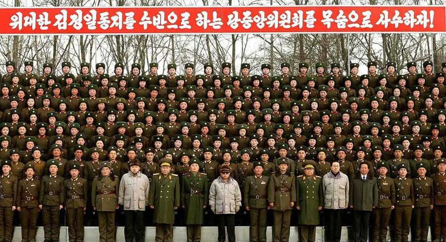 Udateret fotografi af den nordkoreanske leder Kim Jong-Il sammen med officerer og soldater fra den koreanske folkefærs 2670. enhed.