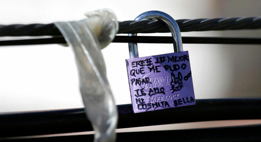 A padlock and a condom are seen around cables along the bridge of the Americas in La Paz September 2, 2014. Lovers leave behind padlocks written with their names and dedications at the bridge, which is also a popular place for married couples, but it is also a place where young people commit suicide by jumping off the bridge. September is celebrated as the month of love in Bolivia. REUTERS/David Mercado (BOLIVIA - Tags: SOCIETY HEALTH)