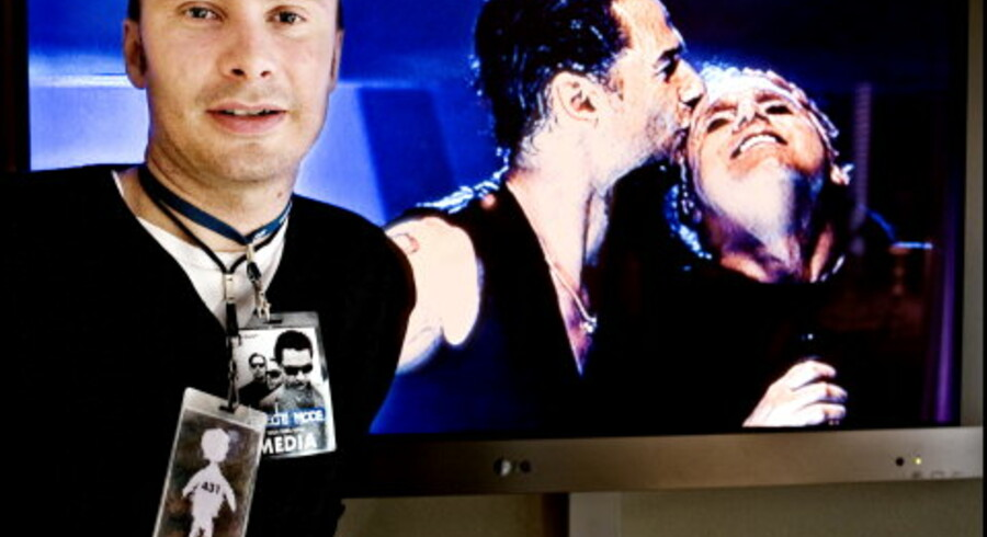 John Schackinger Hansen med hans to VIP-kort om halsen. De er hans livline, der kan skaffe ham backstage ved koncerterne. Bag ham kører på fladskærmen februar-koncerten fra Milano med forsangeren Dave Gahan (tv.) og sangskriveren og guitaristen Martin Gore. Foto: Linda Henriksen