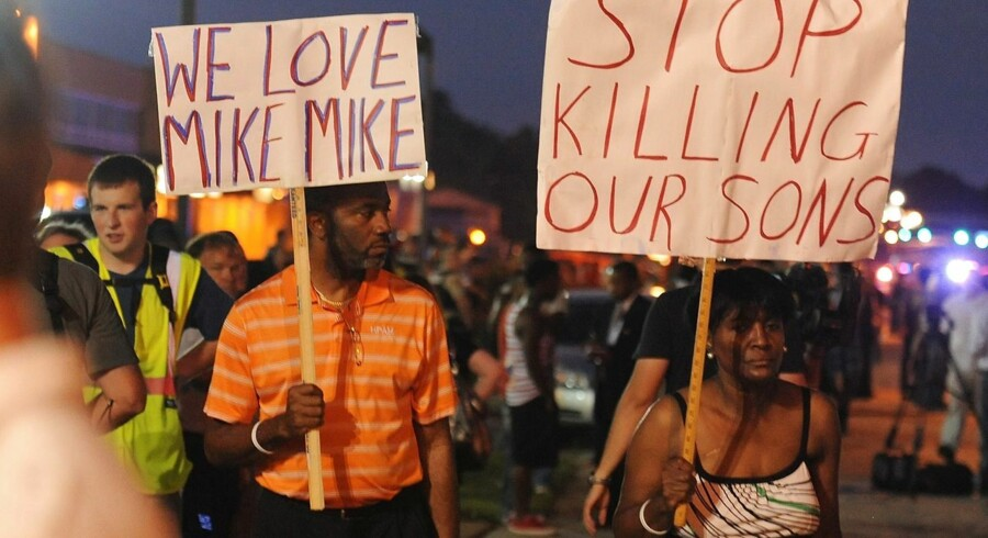 Demonstrators display signs during a protest on West Florissant Avenue in Ferguson, Missouri on August 18, 2014. Police fired tear gas in another night of unrest in a Missouri town where a white police officer shot and killed an unarmed black teenager, just hours after President Barack Obama called for calm. AFP PHOTO / Michael B. Thomas