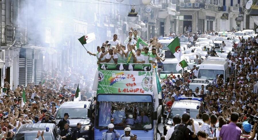 Algeriets VM-landshold blev kørt gennem hovedstaden Algier i åben bus og hyldet som helte.