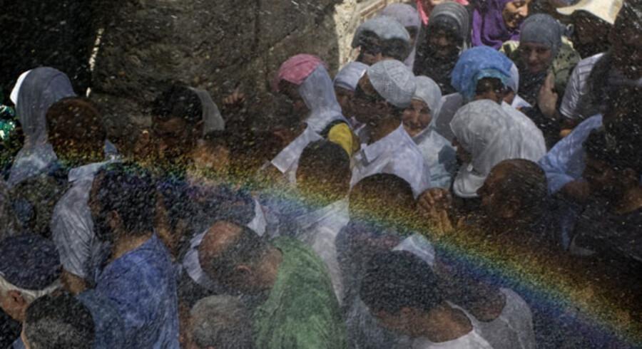 En gruppe palæstinensere lader sig afkøle i vandet fra en sprinkler ved Al-Aqsa-moskeen i Jeruselem, hvor sommerheden slår nye rekorder. Lige så hede er USAs og Mellemøstkvartettens fredsdrømme forud for de direkte forhandlinger i Washington 2. september.