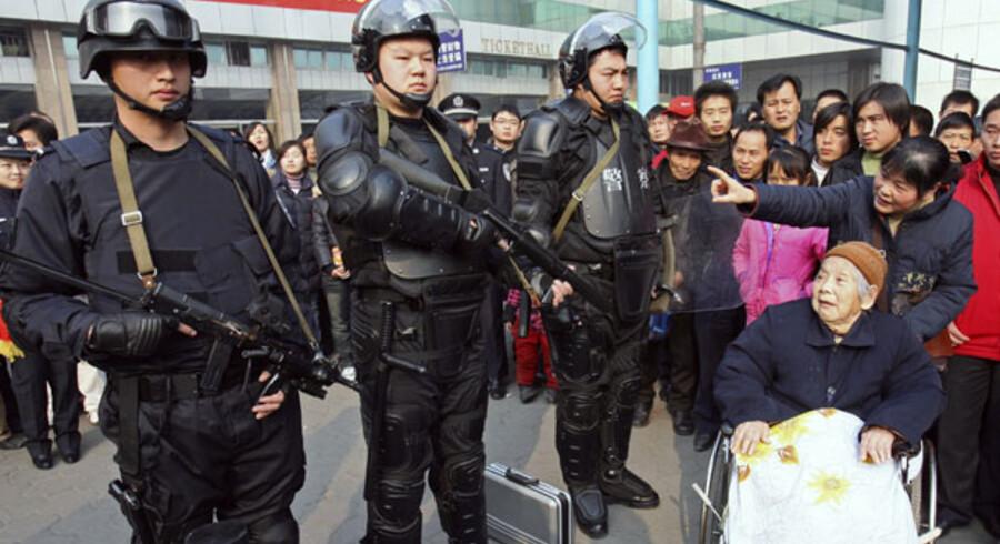 Politistyrken i Wuhan er udstyret med andet end knipler – her reklamerer korpset for sit nyeste isenkram foran byens hovedbanegård.