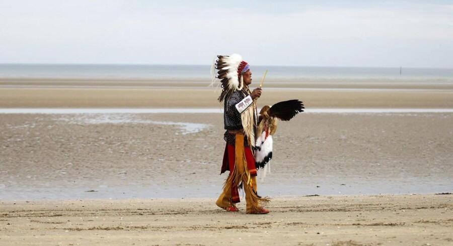 """Det bragte minder om gamle cowboyfilm og stranden hed da også Utah Beach. Men det var Normandiet i Frankrig, der var skuepladsen, da efterkommere af comanche-indianere indtog Utah Beach, som et led i markeringen af 70 årsdagen for invasionen i Normandiet. 13 comanche-indianere deltog i invasionen på amerikansk side og havde en helt særlig rolle. De gik under betegnelsen """"Comanche Code Talkers"""" var tilknyttet det 4. signal-kompagni og blev brugt som en form for menneskelig kryptering. De brugte nemlig comanche-sproget til at overføre taktiske beskeder mellem regimenterne, uden at den tyske besættelsesmagt kunne afkode dem.På billedet beder en efterkommer af de 14 comanche-soldater på Utah Beach, i Sainte-Marie-du-Mont, i det nordvestlige Frankrig."""