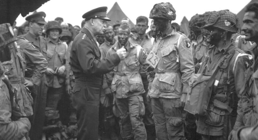 Fredag er det 70 år siden De Allierede gik i land på Normandiets strande i kampen mod Nazityskland.Den amerikanske general og øverstkommanderende for de allierede styrker Dwight D. Eisenhower hilser på de amerikanske faldskærmstropper inden landgangen i Nordmandiet den 6. juni.