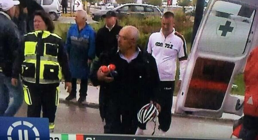 Afsløret: Her prøver stikker en gal souvenir-jæger af med Giampaolo Carusos hjelm og drikkedunke, mens rytteren bliver lagt ind i den ventende ambulance.