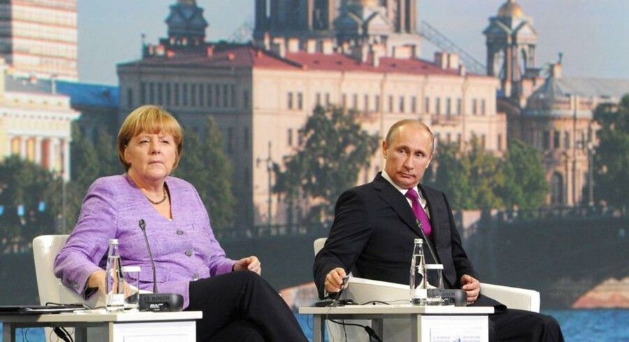Russia's President Vladimir Putin (R) and Germany's Chancellor Angela Merkel sit together as they attend an International Economic Forum in St. Petersburg, on June 21, 2013. Germany said today that plans for Merkel and Putin to jointly open a new exhibition that includes war booty taken by the Red Army from Germany had been called off.AFP PHOTO / RIA-NOVOSTI / POOL/ MIKHAIL KLIMENTYEV