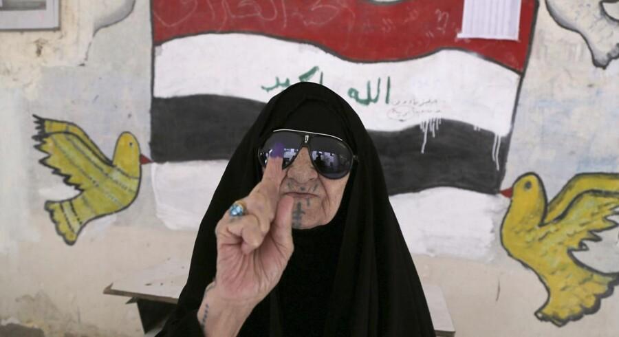 En irakisk kvinde viser sin blæk-dyppede finger ved et valgsted i Bagdad under parlamentsvalget onsdag.