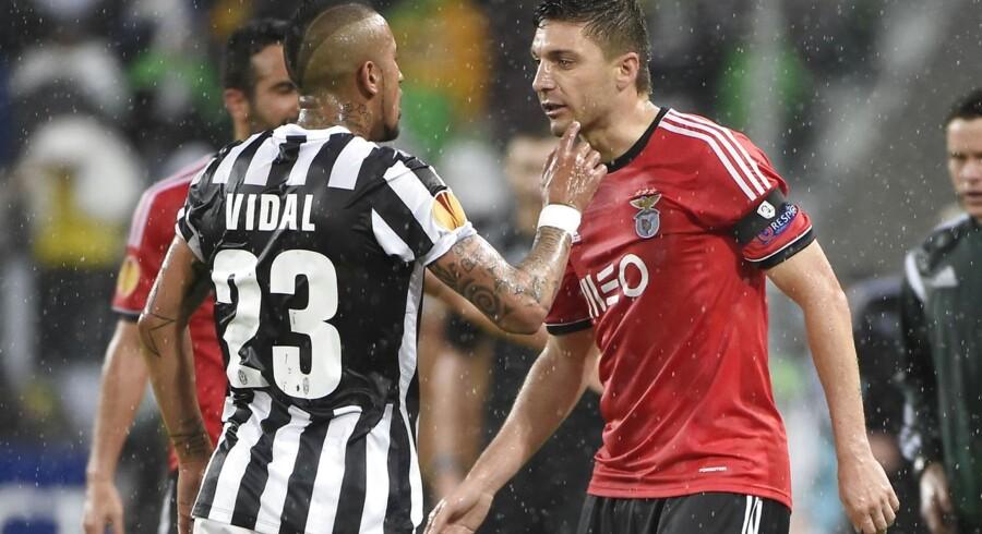Benficas brasilianske forsvarsspillerGuilherme Siqueira, til højre, i infight med Juventus' chilenske midtbanespiller Arturo Vidal i torsdag aftens dramatiske Europa League-semifinale.