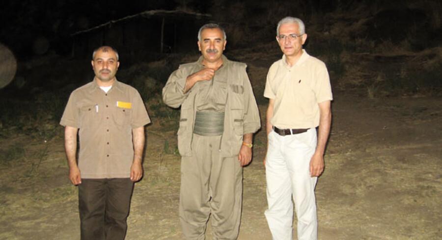 På dette billede fra en PKK-lejr i Nordirak ses den øverste PKK-leder Murat Karayilan i midten. Til højre står daværende direktør for ROJ TV, Manouchehr Zonoozi, til venstre Metin Yüce, direktør for ROJ TVs leverandør af nyhedsprogammer, ROJ NV.