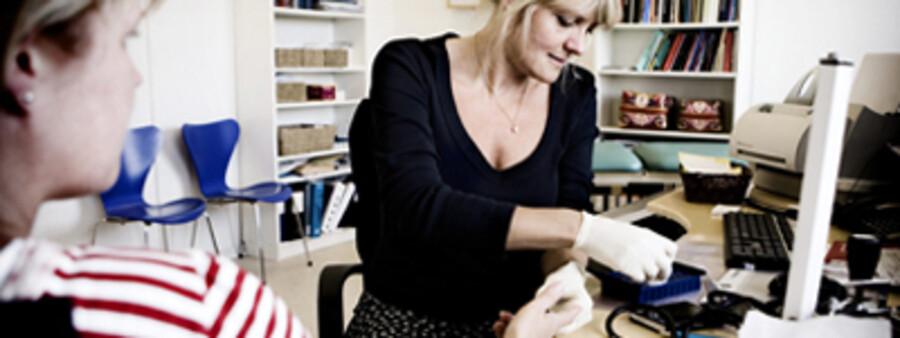 Helle Fals (th.) er sammen med fem andre praktiserende læger gået sammen i lægehuset Lægerne i Amager Centret. Her tager hun blodprøve på en patient. Foto: Kristian Sæderup