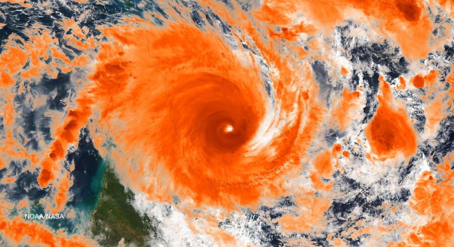 En kraftig cyklon med vindstød på op til 225 kilometer i timen har fredag ramt kysterne i det nordlige Australien, hvor titusinder af mennesker har barrikaderet sig.