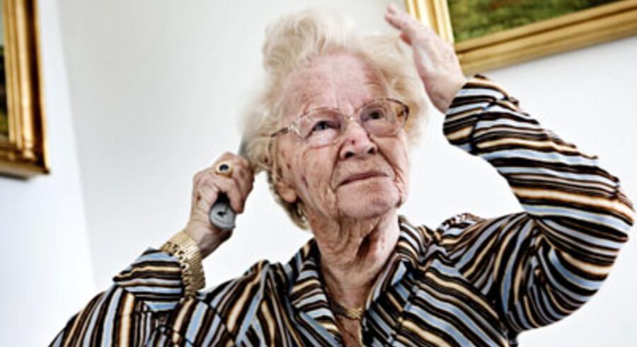 88-årige Emma Rahr friserer lokkerne efter morgentoilettet. Så får hun deodorant på under skjorten og et pift af parfumen »Tommy Girl«.<br>