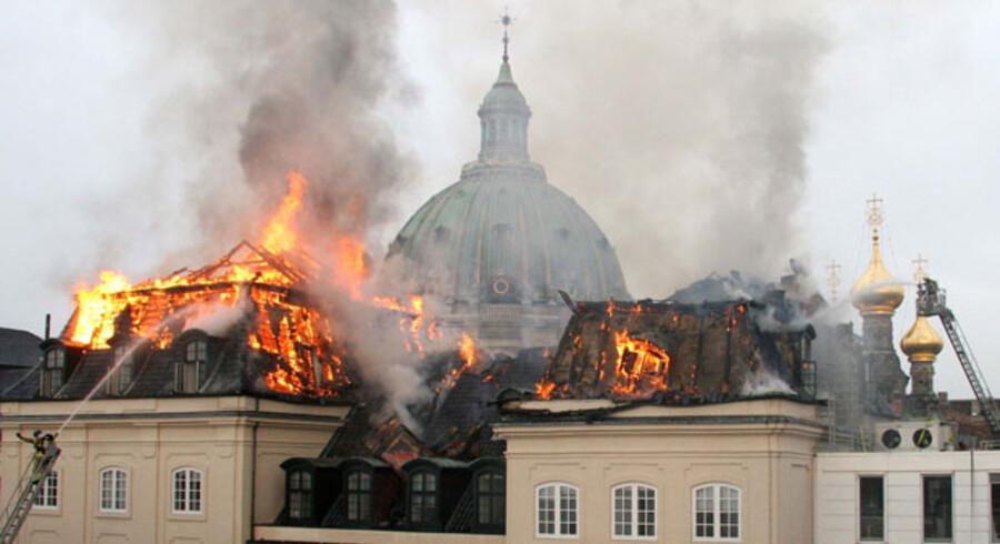 Tagkonstruktionerne i flammer på Dehns Palæ. I baggrunden Marmorkirken og spirene fra Den russiske Kirke.