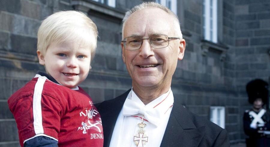 Landsdommer i Østre Landsret, Otto Hedegaard Madsen, takkede for kommandørkorset. På armen var barnebarnet Holger på knap tre år iklædt en t-shirt købt til lejligheden på Amalienborg