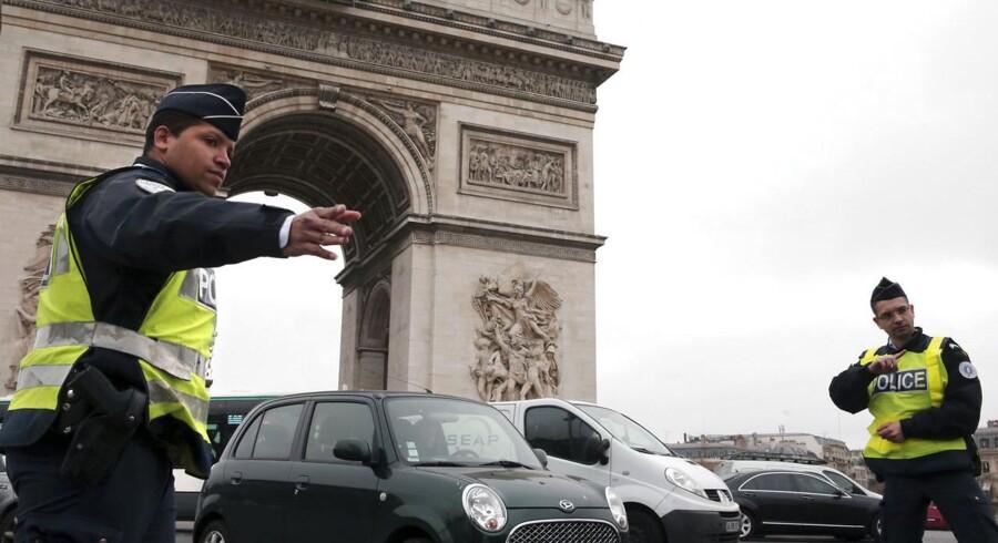 Franske politibetjente kontrollerer biler med lige nummerplader ved Triumfbuen, som ikke havde lov til at køre i hovedstaden Paris mandag.