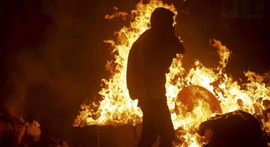 En demonstrant går igennem de brændende gader i byen Caracas. Oprørslederen Leopoldo Lopez overgav sig selv til politiet tirsdag, hvilket udløste enorme protester og demonstrationer.