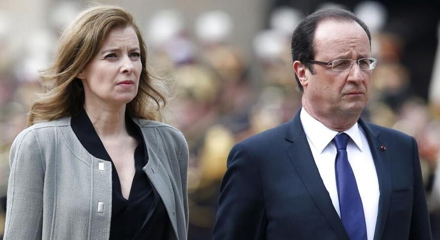 ARKIVFOTO. Francois Hollande og hans nu tidligere kæreste Valérie Trierweiler er stramme i maskerne under en mindeceremoni i juni sidste år.