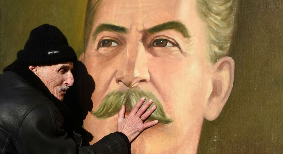 A man touches the portrait of Soviet leader Joseph Stalin, during a ceremony marking his 137th anniversary, in Gori, on December 21, 2016. . Vano Shlamov / AFP
