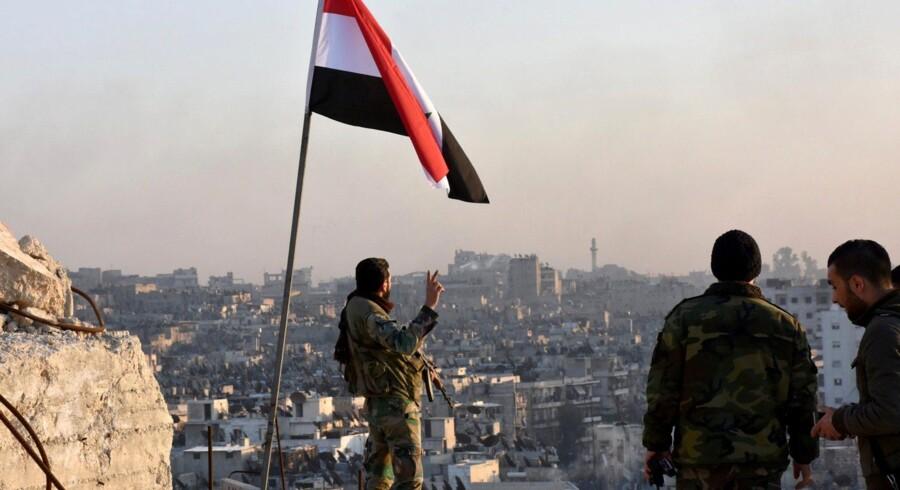 En syrisk soldat gør V-tegnet for sejr under Syriens flag, mens han ser ud over det østlige Aleppo, hvor militæret har tilføjet oprørerne det største nederlag i storbyen siden 2012. Reuters/Sana