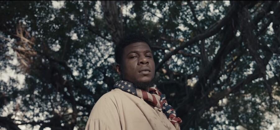 Mick Jenkins med det amerikanske flag som en løkke om halsen. Still fra musikvideoen til »Drowning«.