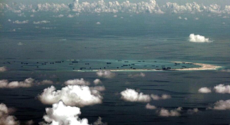 Dette billede fra 2015 viser angiveligt kinesiske fartøjer, der arbejder på at anlægge en kunstig ø i Det Sydkinesiske Hav ud for den filippinske ø Palawan. Kina gør krav på store områder af Det Sydkinesiske Hav, og har trods en domstolsafgørelse ikke i sinde at slække på sin håndhævelse af egen sikkerhed og interesser i området, lød det i går. Arkivfoto: Ritchie B. Tongo / EPA