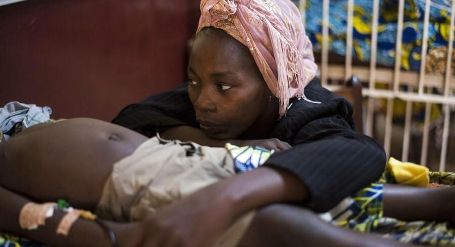 ARKVIFOTO. En kvinde sidder ved siden af sin søn, der lider af malaria.