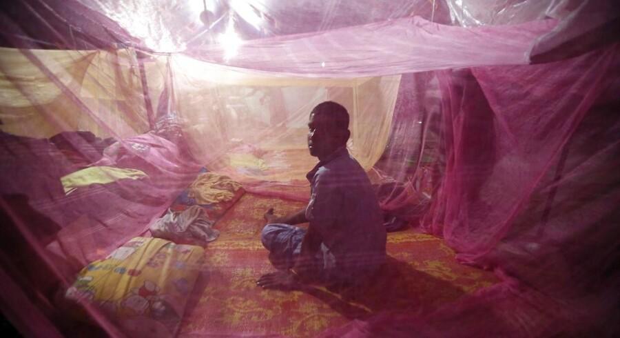 En mand sidder under et myggenet for at beskytte sig imod malariamyggene i en flygtningelejr i Indonesien.