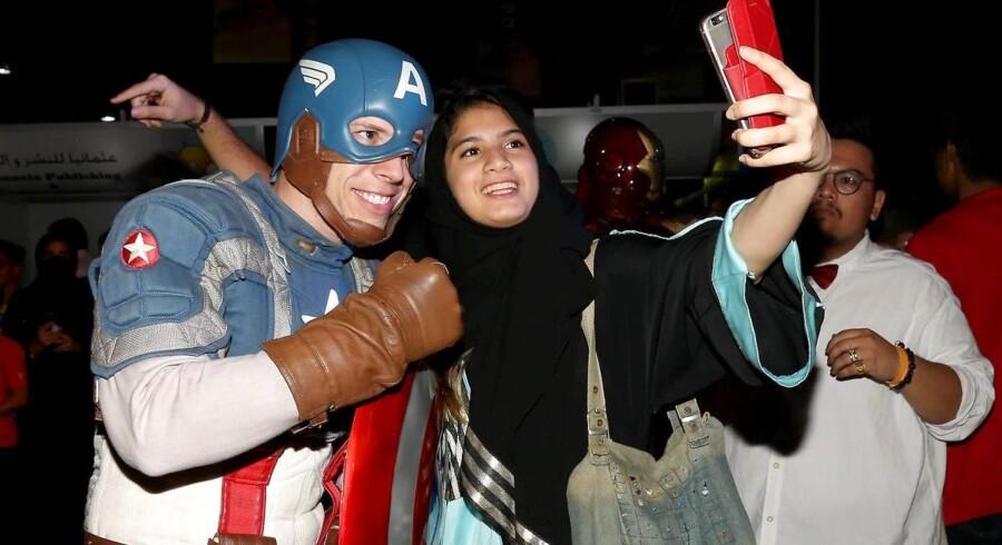 En deltager i Captain America-kostume svinger næven til et billede med en fremmødt fan under Comic Con i Jeddah, Saudi-Arabien