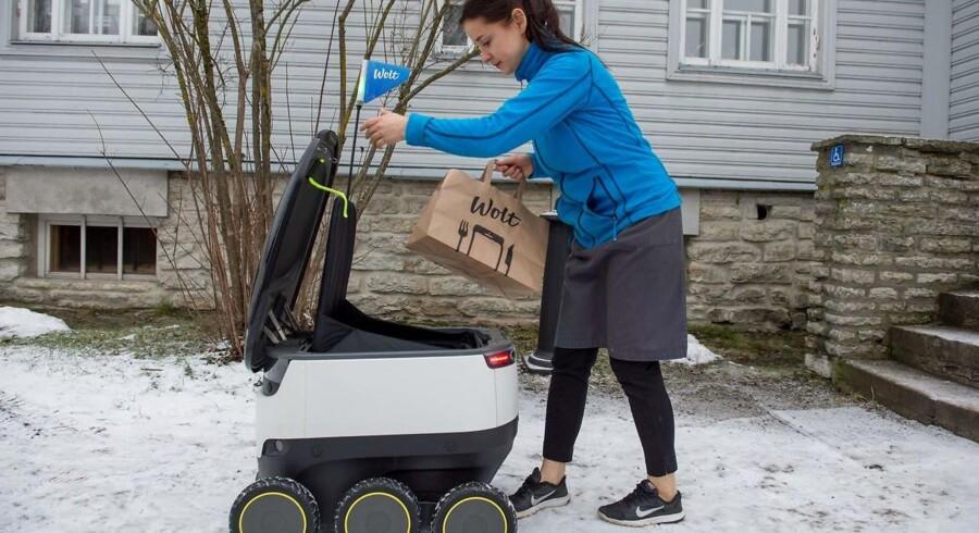 En kvinde i Estlands hovedstad Tallinn modtager sin ordre fra en udbringningsrobot. Det estiske parlament har for to uger siden vedtaget en lov, der gør de små firhjulede budbringere lovlige i gadebilledet. En lov der kommer til at gavne det estiske robotfirma Starship Technologies, der bl.a. er stiftet af danske Janus Friis. Arkivfoto.