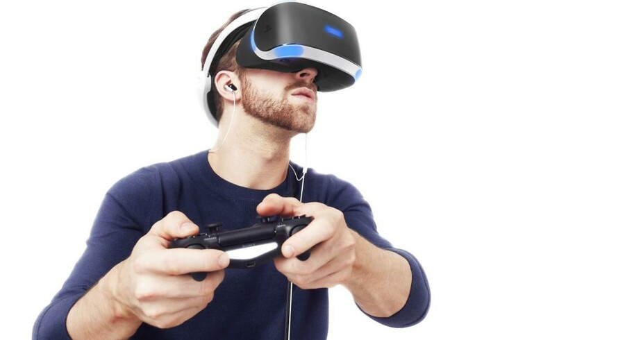 Det kan virke ret sært at se på, at andre er forsvundet ind i den virtuelle virkelighed og kan gå rundt i spil, men oplevelsen inde i brillerne fascinerer - og nu vil Apple måske også stige på vognen. Her er det Sonys Playstation VR-briller, der afprøves. Arkivfoto: Sony/Scanpix