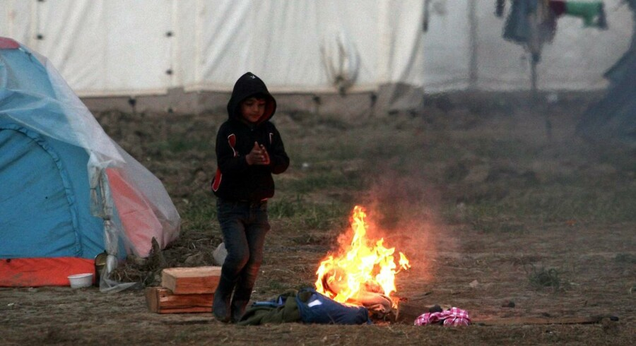 Et barn varmer sig ved et bål i en lejr ved den græsk-makedonske grænse nær Idonemi 27. marts.