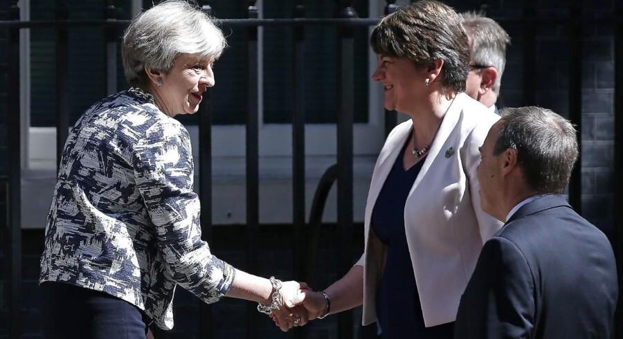 Englands premierminister Theresa May (tv) giver hånd til leder af det nordirske Demokratiske Unionistparti, Arlene Foster (i midten). De to politiske ledere har netop opnået enighed om en regeringsaftale. Theresa Mays eget parti, de konservative, kan ikke selv danne flertal i det engelske parlament, hvor Labour med Jeremy Corbyn i front havde en stor og overraskende fremgang ved det nylige valg.
