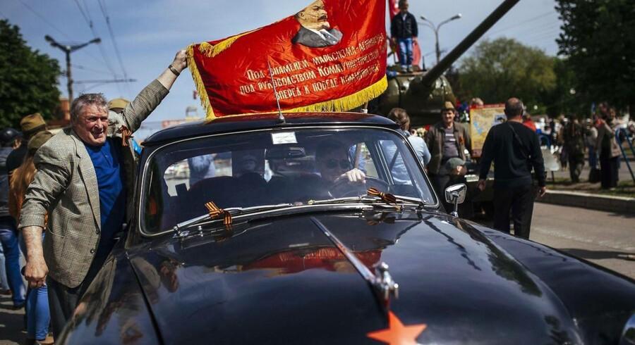 En mand vajer et flag med tidligere Sovjet-leder Vladimir Putin i den ukrainske by Lugansk.