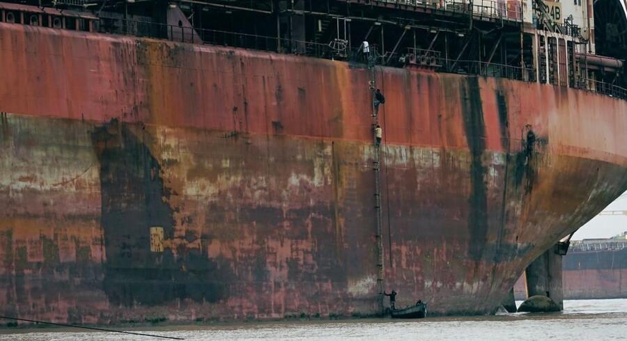 Her ligger det engang Mærsk-ejede skib North Sea Producer på en strand i Bangladesh, mens arbejdere uden faldsikring er på vej op ad skibets side.