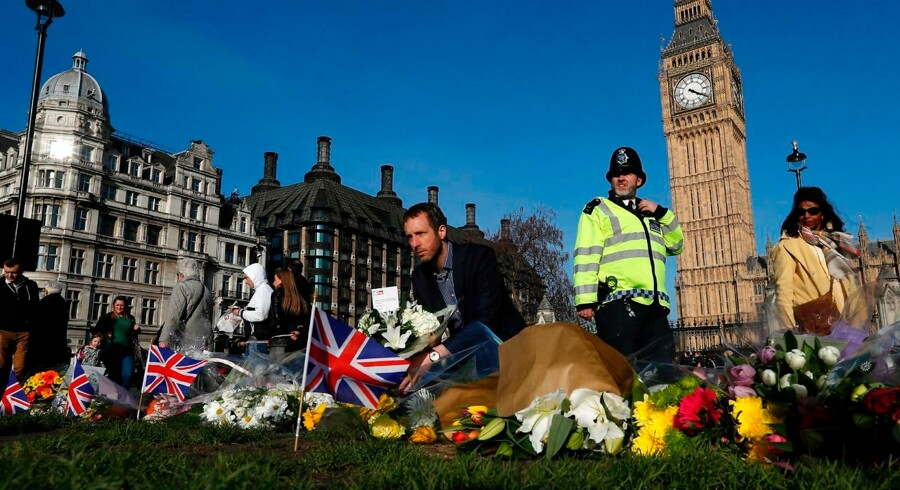 """People lay floral tributes to the victims of the March 22 terror attack in Parliament Square outside the Houses of Parliament in central London on March 24, 2017. British police said on March 24 they had made two further """"significant"""" arrests over the Islamist-inspired terror attack on parliament, as they appealed for information about the homegrown killer who left four people dead. Nine people are now in custody over the March 22 rampage in Westminster, in which at least 50 people were injured, 31 requiring hospital treatment, counter-terrorism commander Mark Rowley said. / AFP PHOTO / Adrian DENNIS"""